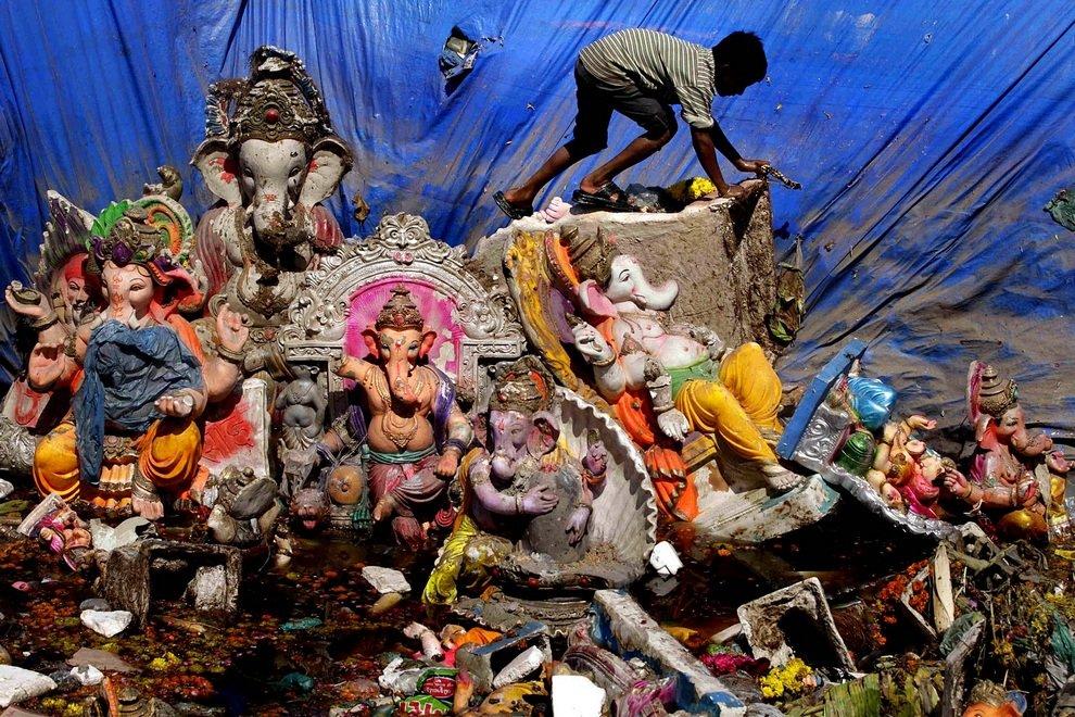 Мальчик ходит среди многоразовых идолов Ганеши на следующий день после фестиваля «Ганеша-чатуртхи», во время которого идолы опускались в воду как символ рождения божества и смывания всех бед человечества, Ахмадабад, Индия.